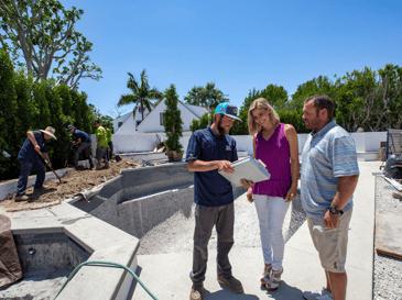 Professional landscape designer and planting crew landscaping backyard near pool